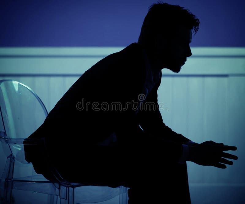 Trauriger Mann, der auf dem Stuhl stationiert stockbilder