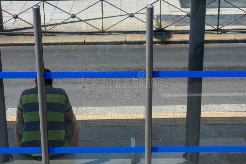 Trauriger Mann, der an der blauen abgestreiften Bushaltestelle am sonnigen Tag sitzt lizenzfreie stockfotografie