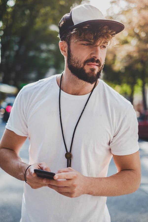 Trauriger Mann, der draußen Handy hält lizenzfreies stockbild