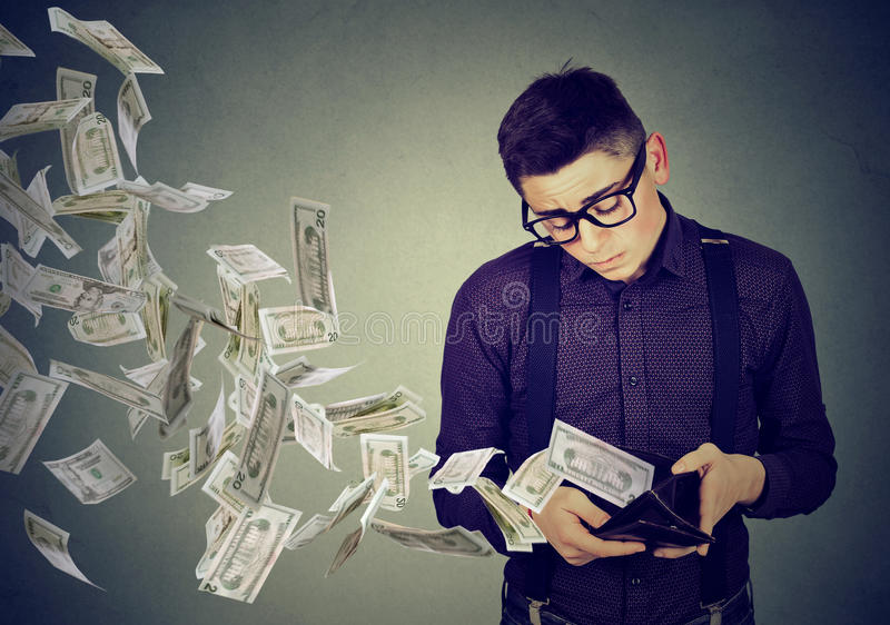 Trauriger Mann, der Geldbörse mit den Gelddollarbanknoten weg fliegen betrachtet stockfotografie