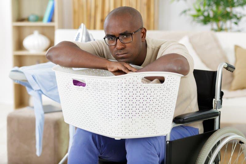 Trauriger Mann im Rollstuhl, der Wäscherei tut lizenzfreies stockfoto