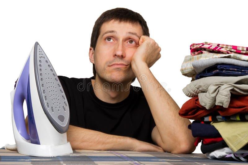 Trauriger Mann, Wäschekleidung und Eisen stockfotografie