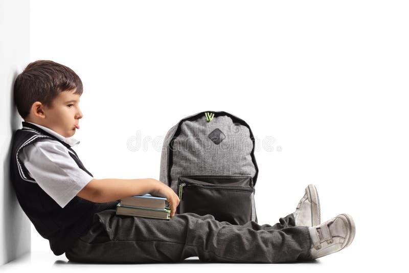 Trauriger Schüler mit einem Rucksack und Büchern stockbilder
