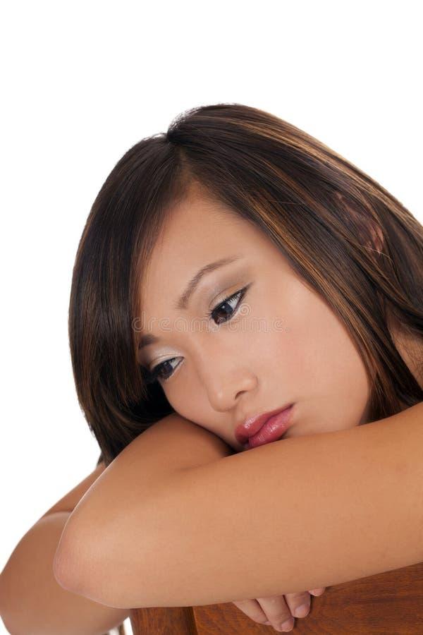 Trauriger schauender asiatischer jugendlich Mädchenkopf auf Armen stockfotos