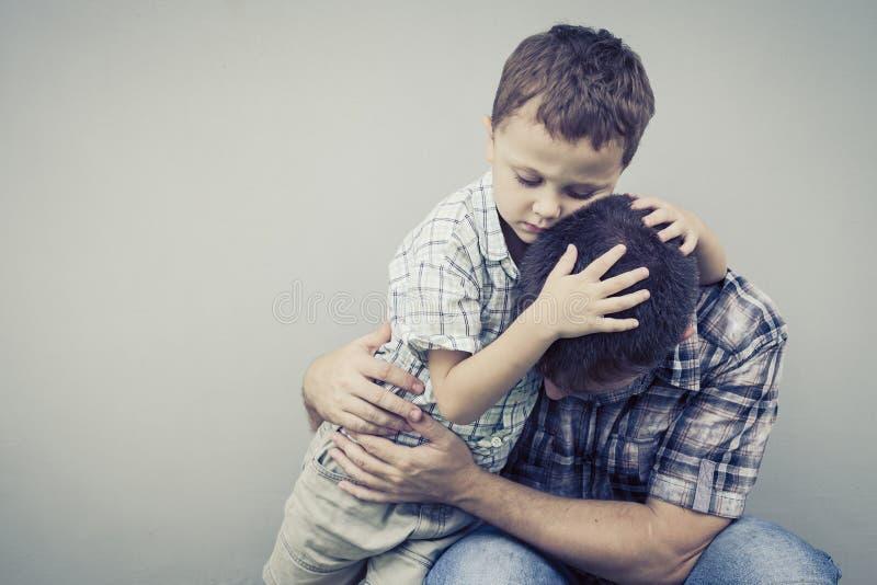 Trauriger Sohn, der seinen Vati nahe Wand umarmt lizenzfreies stockfoto