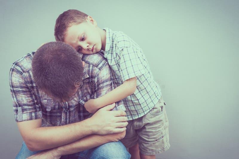 Trauriger Sohn, der seinen Vati nahe Wand umarmt stockbilder