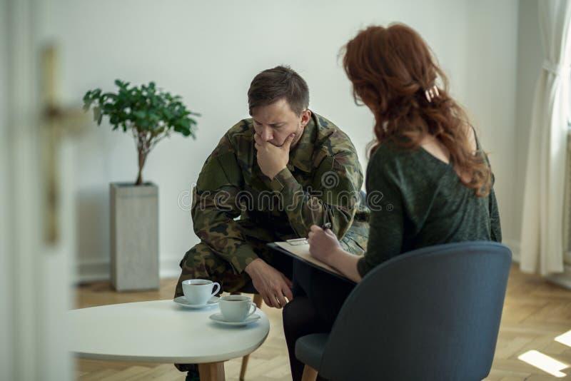 Trauriger Soldat, der seinen Mund bei der Unterhaltung mit seinem Therapeuten bedeckt lizenzfreie stockbilder