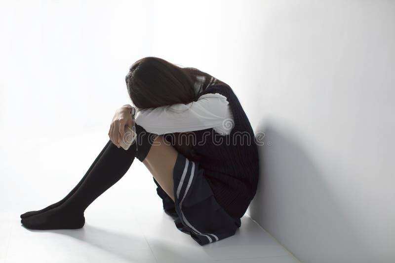 trauriger Student, der Handy hält und auf dem flo sitzt lizenzfreies stockfoto