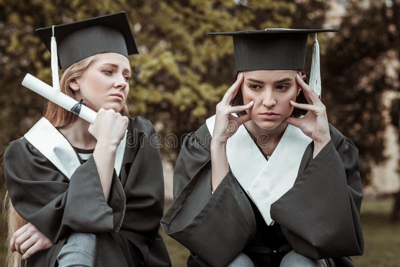 Trauriger Student, der nahe ihrem Gruppenkameraden sitzt stockfotografie