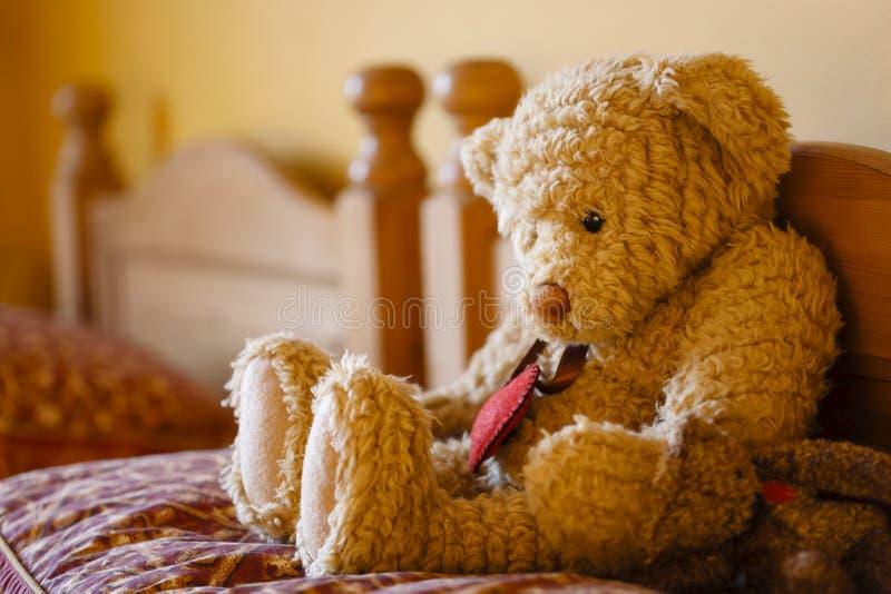 Trauriger Teddybär betreffen ein Bett lizenzfreies stockfoto