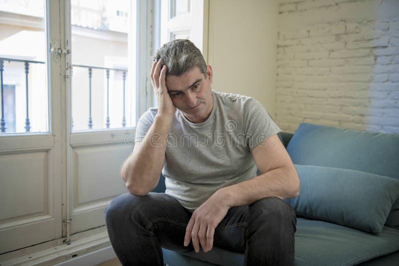 Trauriger und besorgter Mann mit dem grauen Haar, welches zu Hause das Couchschauen sitzt lizenzfreies stockfoto