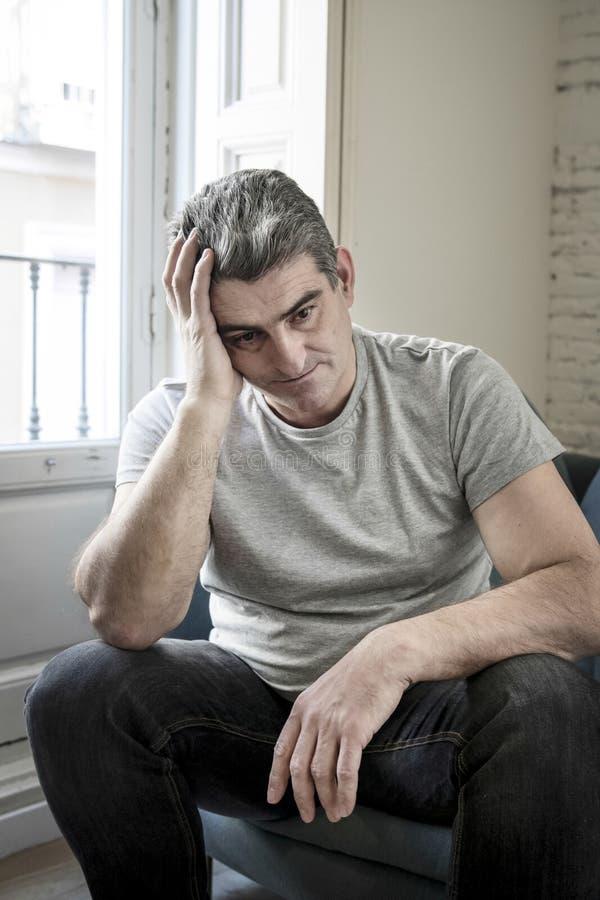 Trauriger und besorgter Mann mit dem grauen Haar, welches zu Hause das Couchschauen sitzt stockfotografie