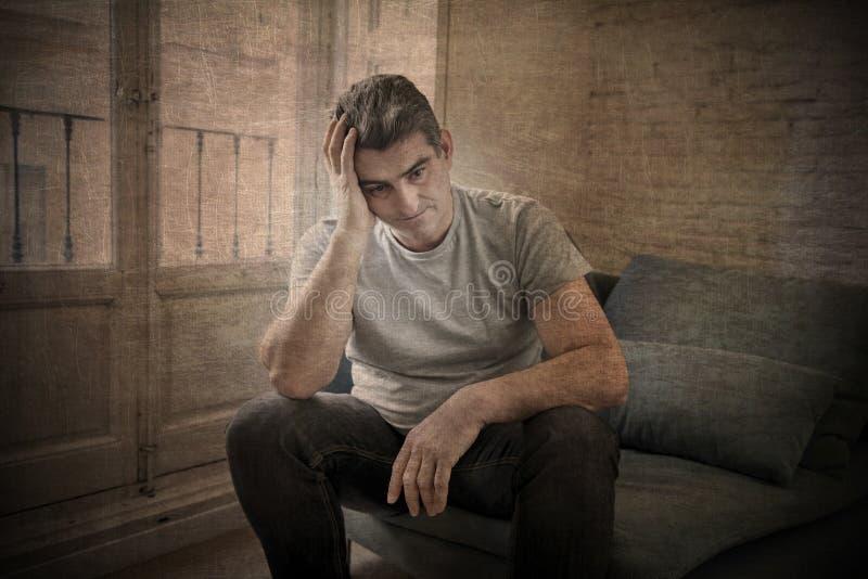 Trauriger und besorgter Mann mit dem grauen Haar, welches zu Hause das Couchschauen sitzt lizenzfreie stockfotos