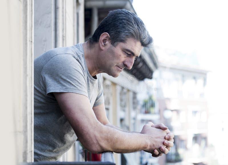 Trauriger und deprimierter Mann 40s, der zu Hause durch Freien balco schaut stockbild