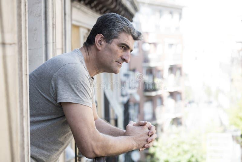 Trauriger und deprimierter Mann 40s, der zu Hause durch Freien balco schaut stockfotografie