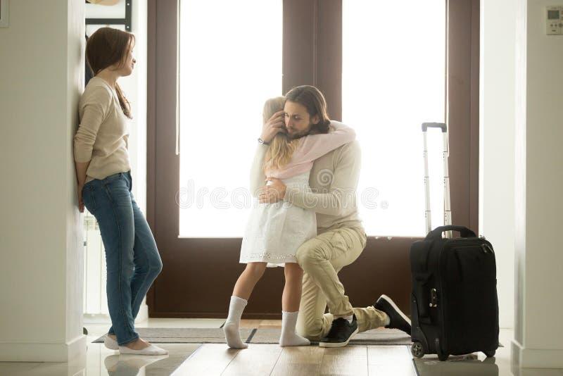 Trauriger Vater, der kleine Tochter bevor dem Gehen für lange Reise umarmt lizenzfreie stockbilder