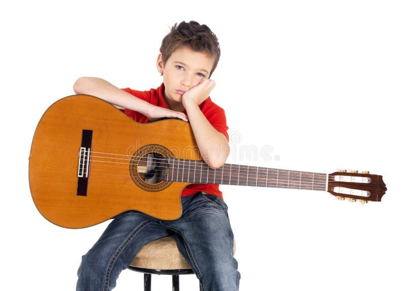 Trauriger weißer Junge mit einer Akustikgitarre stockbilder