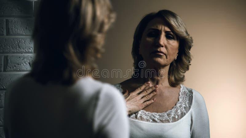 Trauriges älteres weibliches Schauen im Spiegel mit Ekel, alterndes Problem, Unsicherheit lizenzfreies stockfoto