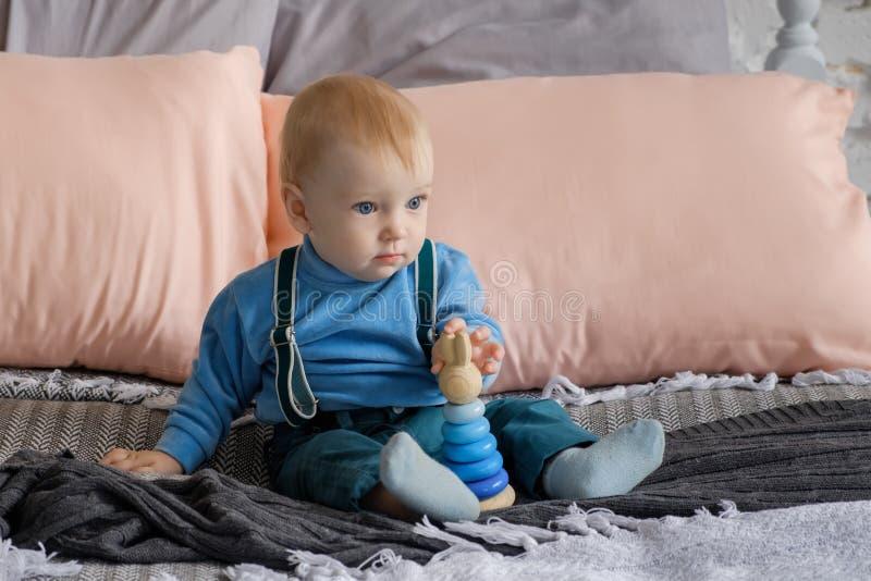 Trauriges, aber schönes blauäugiges Baby, das auf dem Bett nahe bei der Spielzeugpyramide sitzt stockfoto