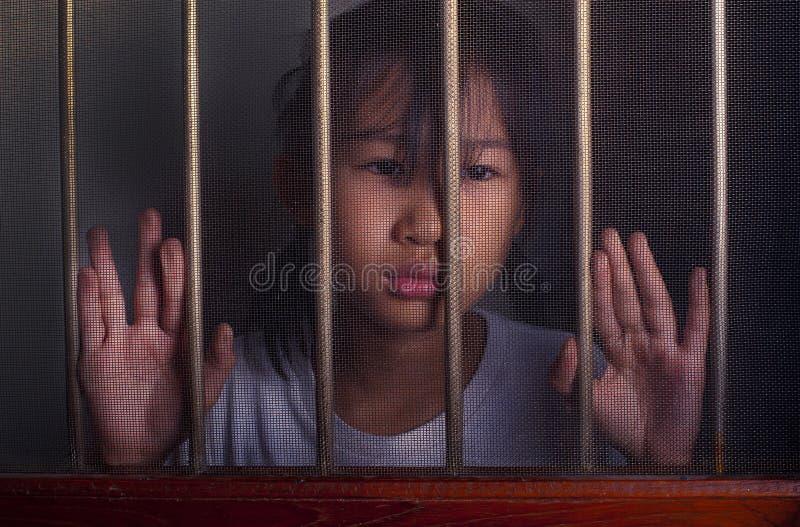Trauriges asiatisches Kind, das hinter dem DrahtFenster steht unglücklich lizenzfreies stockfoto