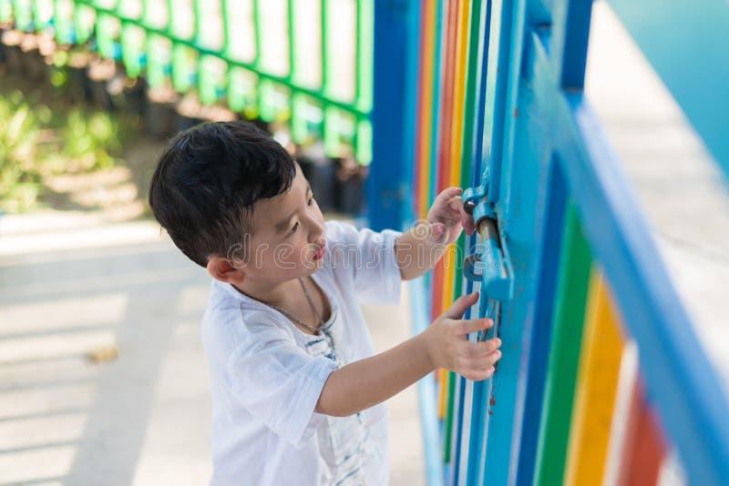 Trauriges asiatisches Kind hinter dem Gitter, das versucht zu entgehen Flacher DOF stockbild