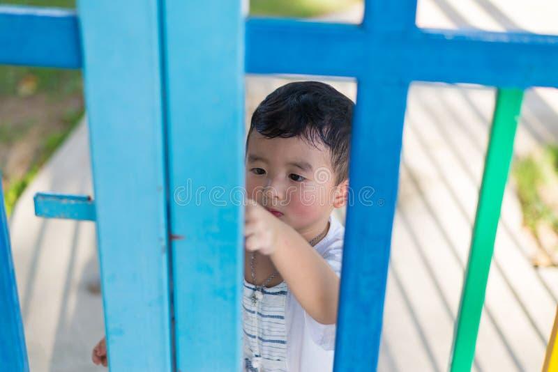 Trauriges asiatisches Kind hinter dem Gitter, das versucht zu entgehen Flacher DOF stockbilder