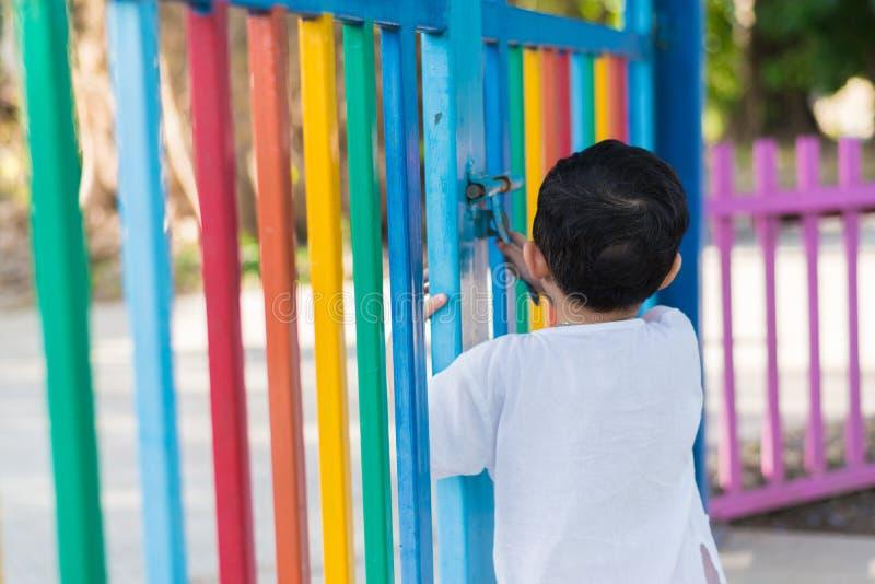 Trauriges asiatisches Kind hinter dem Gitter, das versucht zu entgehen Flacher DOF lizenzfreie stockfotografie