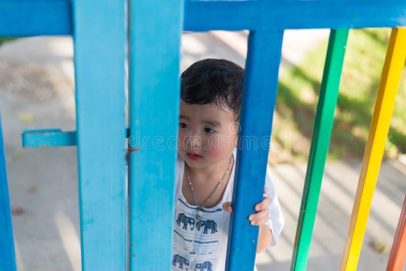 Trauriges asiatisches Kind hinter dem Gitter, das versucht zu entgehen Flacher DOF stockfoto