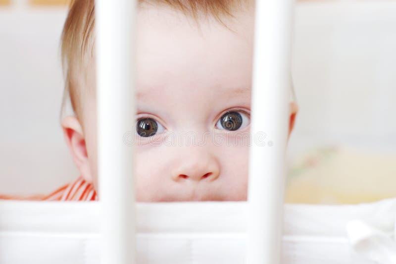 Trauriges Baby im weißen Bett lizenzfreies stockfoto