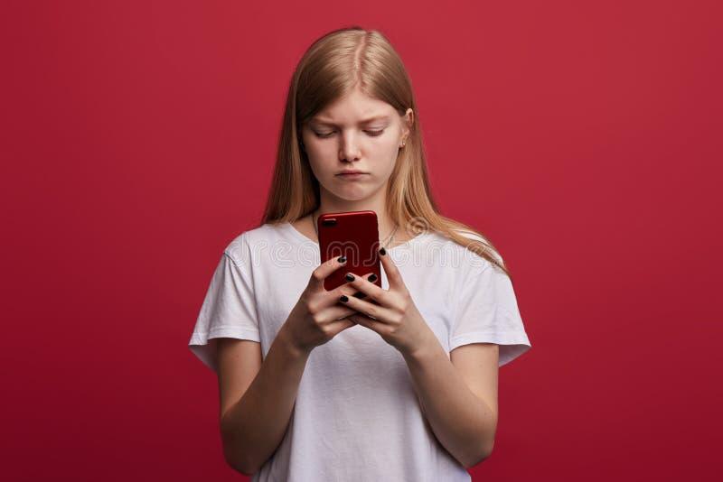 Trauriges deprimiertes Mädchen steht Gebrauch ein Smartphone lizenzfreie stockfotos