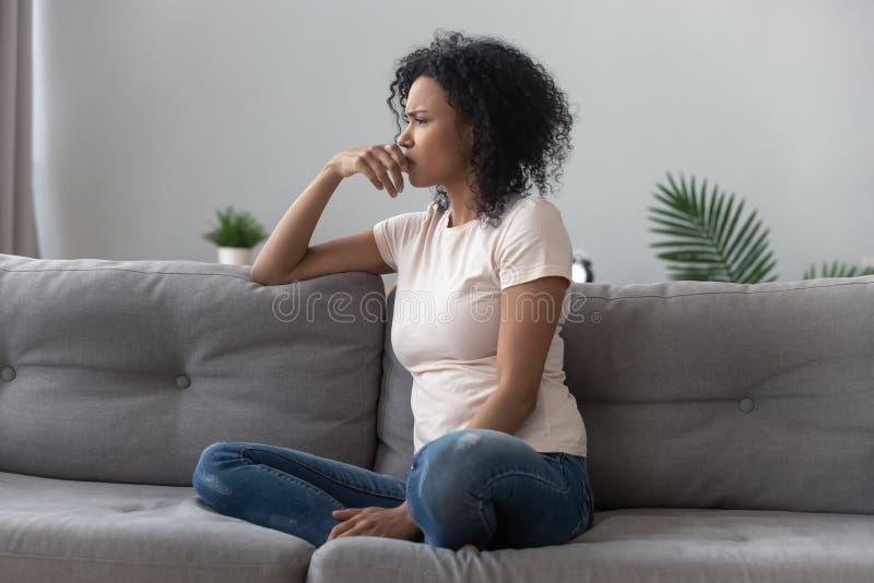 Trauriges durchdachtes afrikanisches Mädchen auf dem Sofa, welches weg das Gefühl deprimiert schaut stockfoto