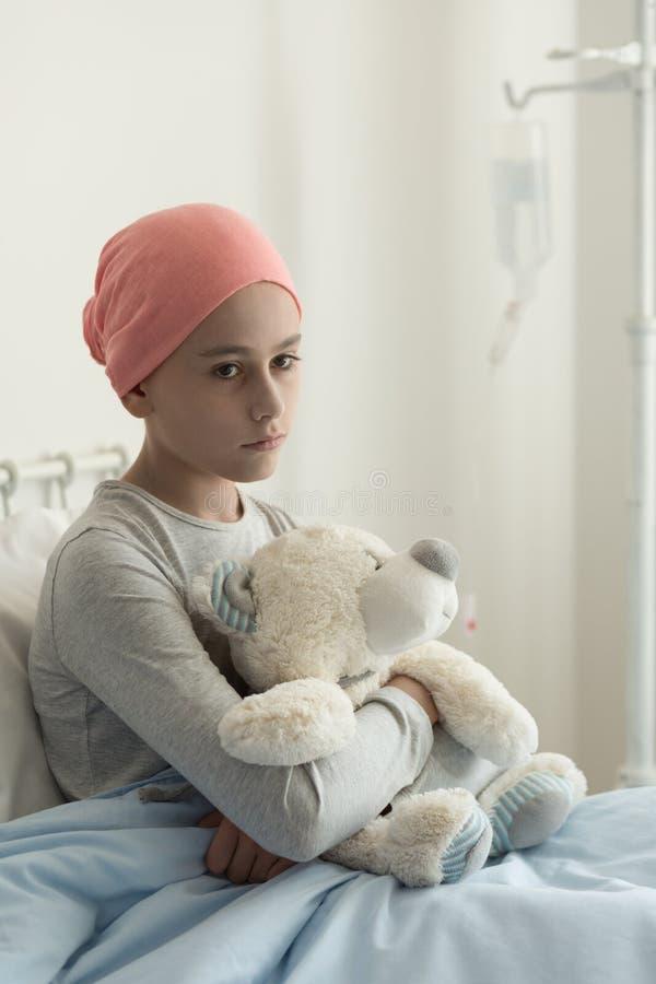 Trauriges einsames krankes Mädchen mit Krebs, der Plüschspielzeug im Krankenhaus umarmt stockbild
