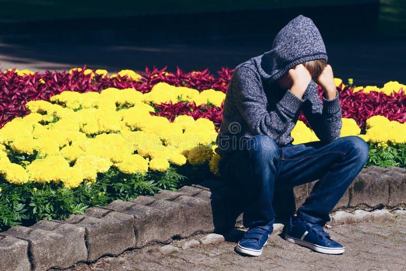 Trauriges, enttäuschtes Kind halten Haupt mit den Händen stockbild