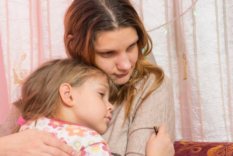 Trauriges Fünfjahresmädchen, das ihre Mutter umarmt lizenzfreies stockfoto