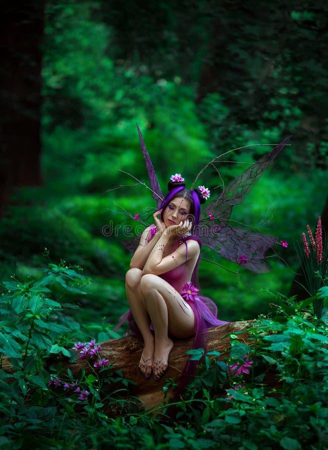 Trauriges feenhaftes Sitzen auf einem Baum stockfoto