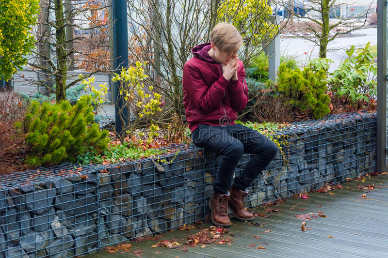 Trauriges jugendlich Jungenbeten im Freien im Stadtpark für zukünftiges Gefühl ner stockfoto