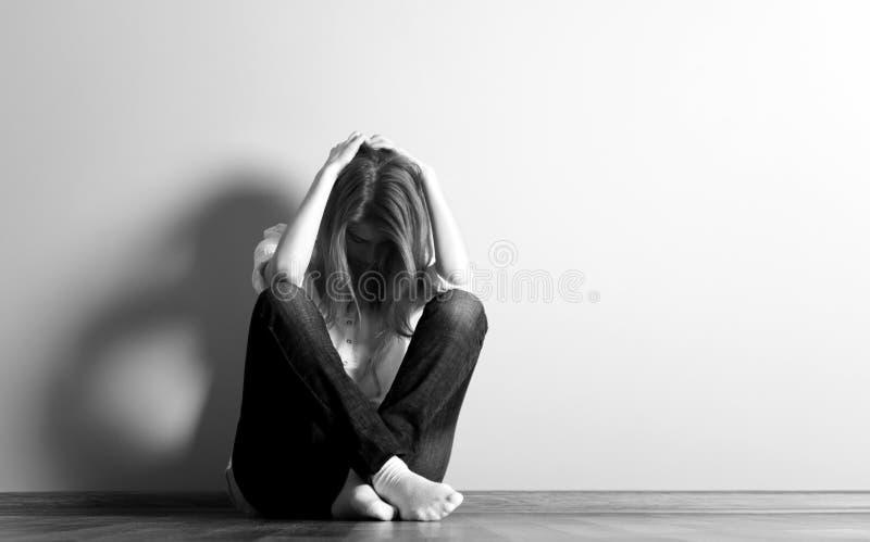 Trauriges jugendlich Mädchen am Fußboden nahe Wand. stockfotos