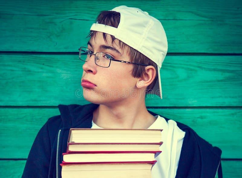 Trauriges jugendlich mit Bücher lizenzfreie stockfotos