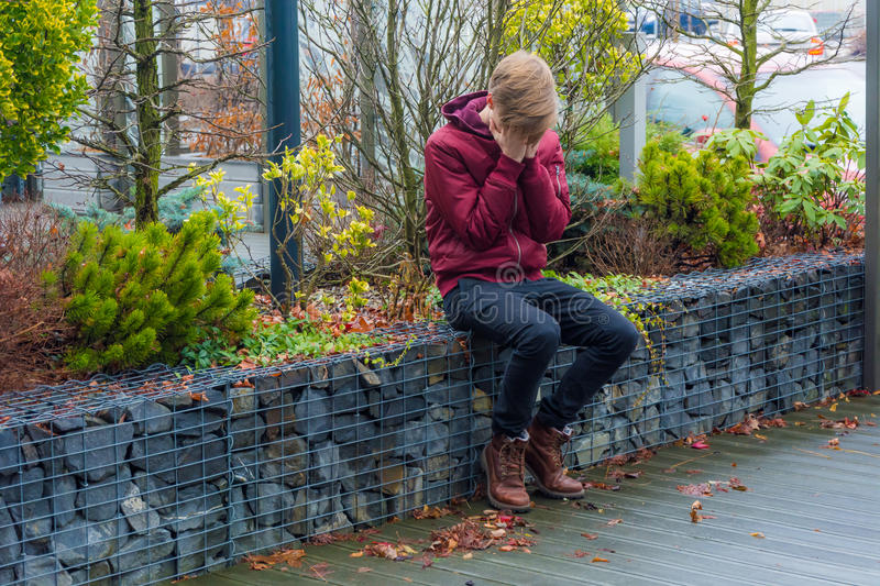 Trauriges Jugendlichjungenschreien im Freien, sein Gesicht mit Handsi bedeckend stockfotos