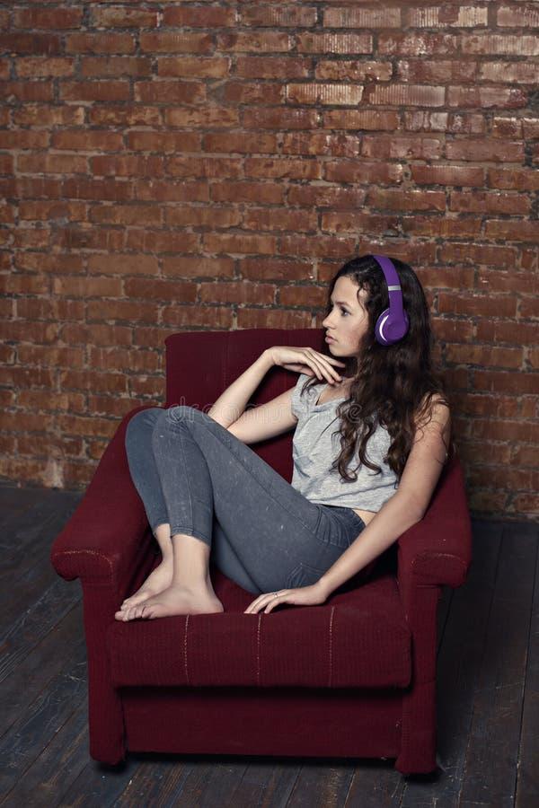 Trauriges Jugendlichmädchen, das Musik auf den zurückschreckenden Kopfhörern selbst in einem alten Stuhl in einem verlassenen Fab lizenzfreie stockfotografie
