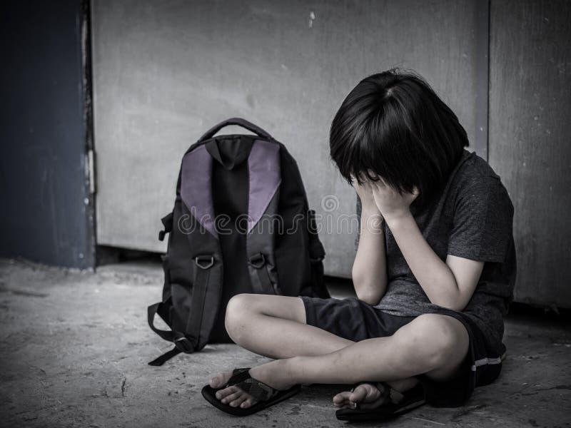Trauriges Kind, das auf dem Boden mit Schultaschewarteelternteil sitzt lizenzfreies stockfoto