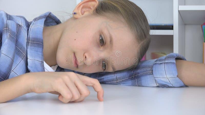 Trauriges Kind, gebohrtes M?dchen, das Finger auf Schreibtisch, betontes ungl?ckliches nicht studierendes Kind spielt lizenzfreie stockfotografie
