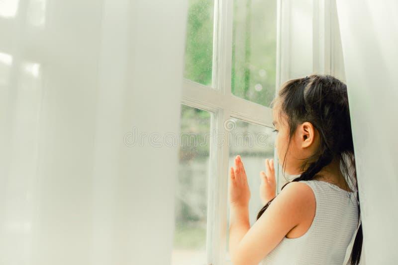 Trauriges Kind, kleines Mädchen, das den Regen schaut lizenzfreie stockbilder