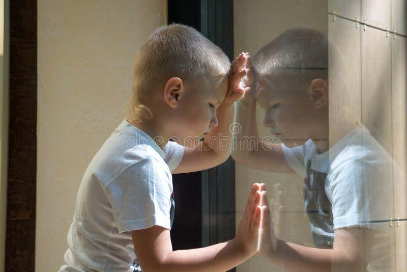 Trauriges Kind nahe Fenster stockbild