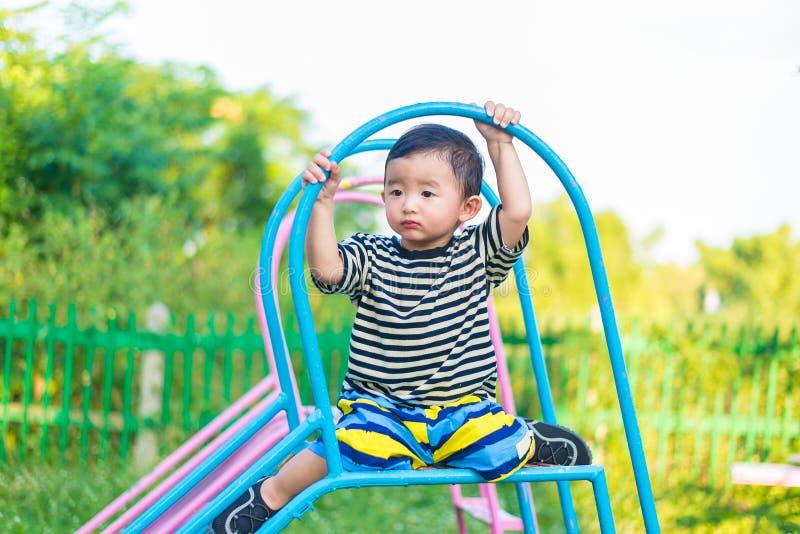 Trauriges kleines asiatisches Kind, das auf Dia am Spielplatz am d sitzt lizenzfreie stockbilder