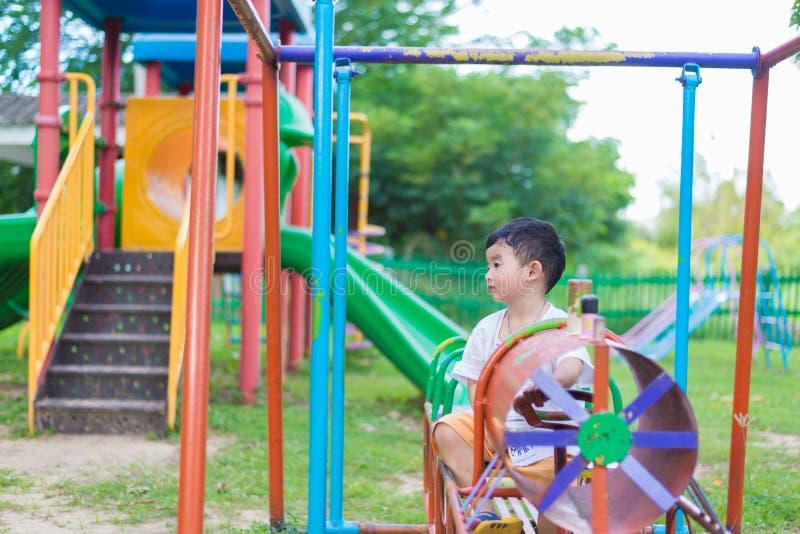Trauriges kleines asiatisches Kind am Spielplatz unter dem Sonnenlicht in der Summe stockbilder