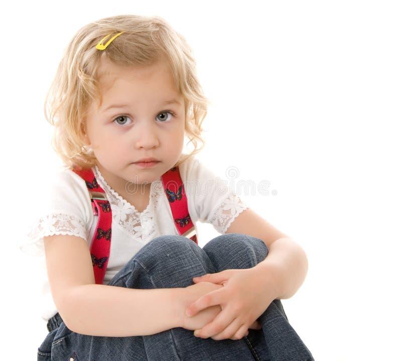 Trauriges kleines blondes Mädchen in den roten Hosenträgern lizenzfreie stockbilder