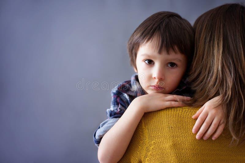 Trauriges kleines Kind, Junge, seine Mutter zu Hause umarmend lizenzfreie stockfotos