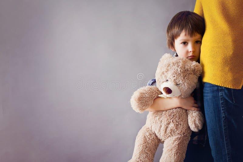 Trauriges kleines Kind, Junge, seine Mutter zu Hause umarmend lizenzfreie stockfotografie