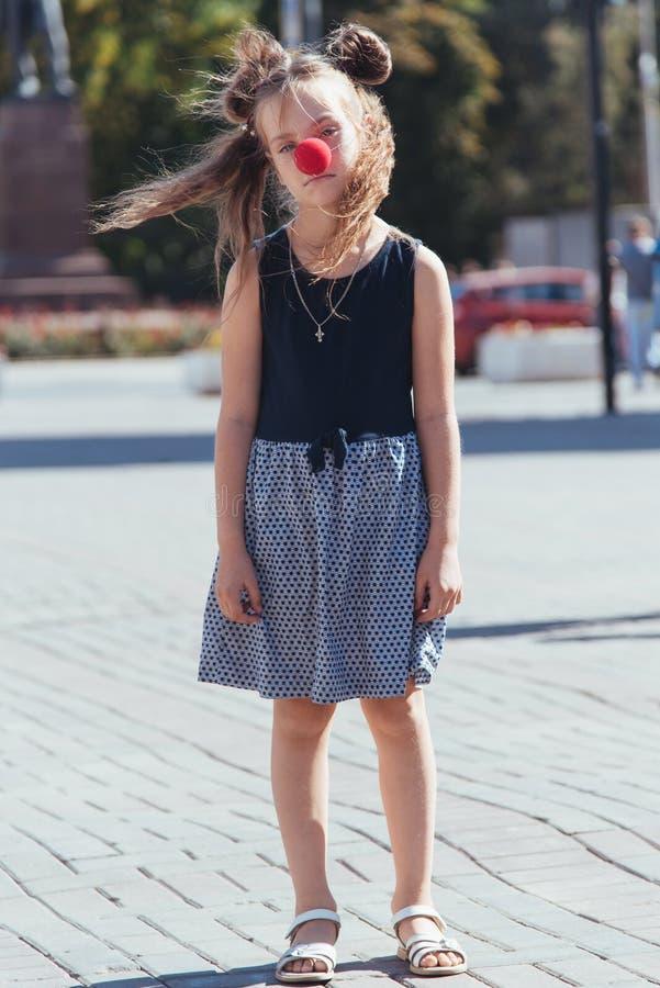 Trauriges kleines Mädchen auf der Straße mit einer Clownnase lizenzfreie stockfotos